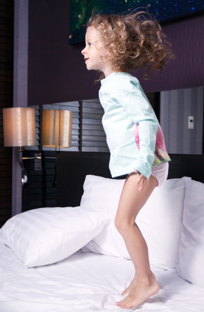 legs crossed at knee: girl jumping on the bed