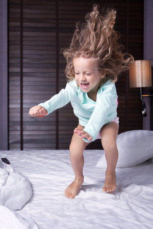 legs crossed on knee: girl jumping on the bed
