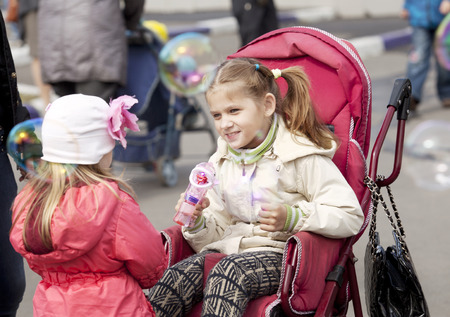 cerebral palsy: a child in a wheelchair in the Park soap bubbles Stock Photo