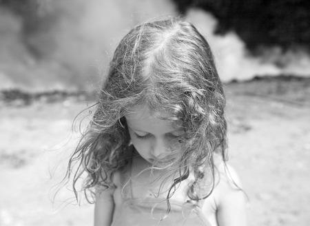 child alone: little girl sad smoke Stock Photo
