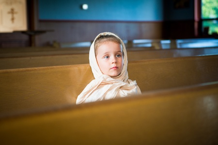 Portrait of the child  girl  sitting on the bench in the orthodox church photo