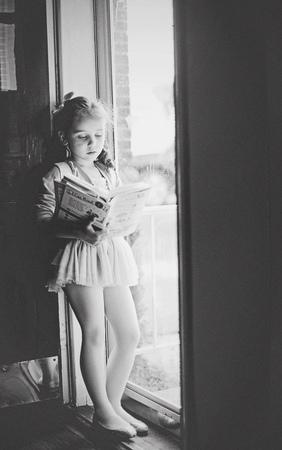 家で本を読む若い幼児の女の子