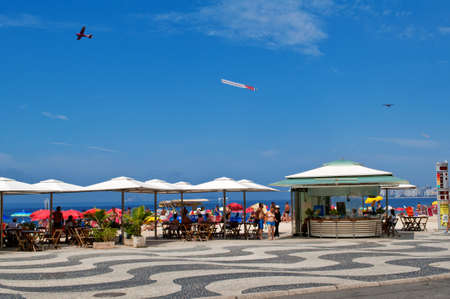 Sunday afternoon - Sunbathers relax walking or having lunch at one of the kiosks located on the Copacabana sidewalk