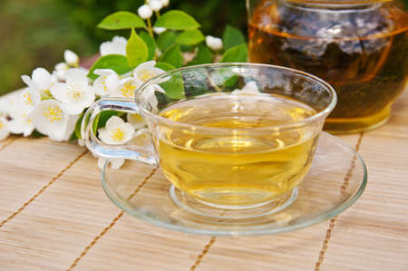 Cup of green tea with branch of jasmine photo