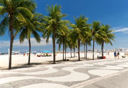 View of Copacabana beach with palms and mosaic of sidewalk in Rio de Janeiro
