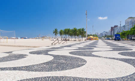 View of Copacabana beach with palms and mosaic of sidewalk in Rio de Janeiro photo