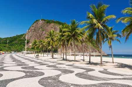 Leme and Copacabana beach with palms and mosaic of sidewalk in Rio de Janeiro
