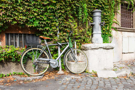 Bicycle parked near drinking tap on the street in Rome, Italy photo