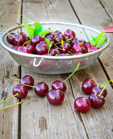 Fresh cherry in colander on wooden table photo