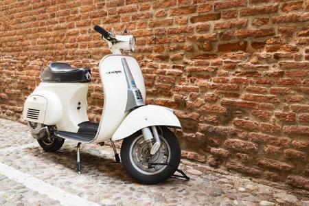 Old Vespa parked on old street in Verona, Italy Redakční