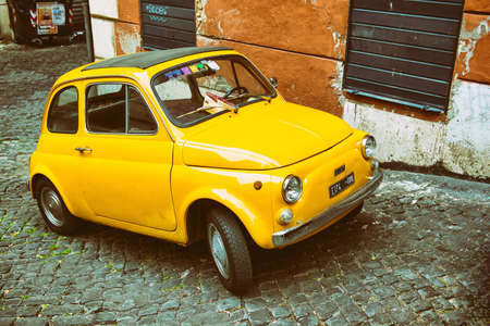 fiat: Yellow Fiat 500 parked in Rome. Italy Editorial