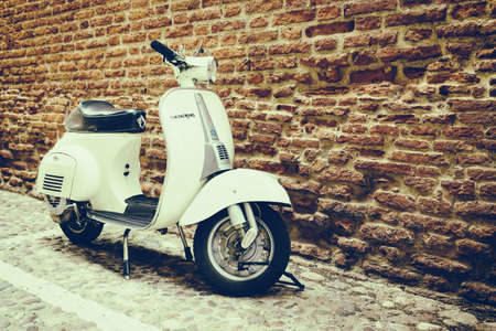 Old Vespa parked on old street in Verona, Italy 報道画像