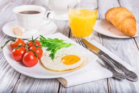 plato de comida: Desayuno con la taza de café, huevo, croissant y jugo de naranja sobre la mesa de madera