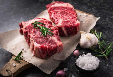 Two raw fresh marbled meat black angus steak ribeye, garlic, salt and  on dark background