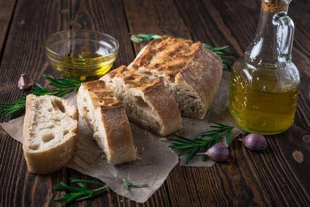 italienisches essen: Geschnittene italienische Brot Ciabatta mit Rosmarin auf Holzuntergrund