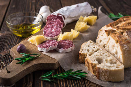 wooden board: Italian bread Ciabatta, salami and cheese Parmesan on wooden cutting board