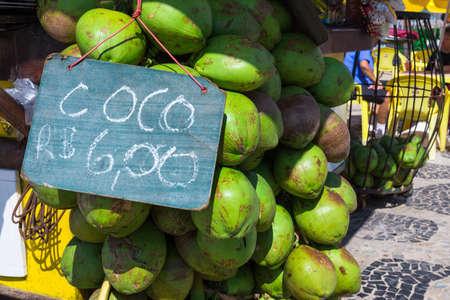 sidewalk sale: Bunch of fresh coco verde (green coconuts) hanging at Ipanema beach sidedwalk in Rio de Janeiro, Brazil