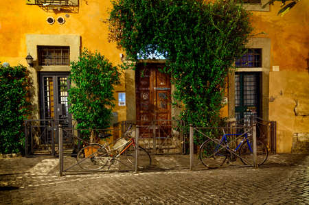 Old street at night in Trastevere, Rome, Italy. Trastevere is rione of Rome, on the west bank of the Tiber in Rome, Lazio, Italy.  Architecture and landmark of Rome