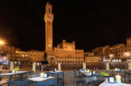 Night view of Campo Square (Piazza del Campo), Palazzo Pubblico and Mangia Tower (Torre del Mangia) in Siena, Tuscany, Italy