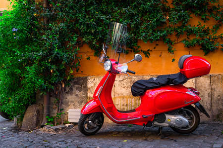 Rome, Italy - September 23, 2016: Red Vespa scooter parked on old street in Rome, Italy Editorial
