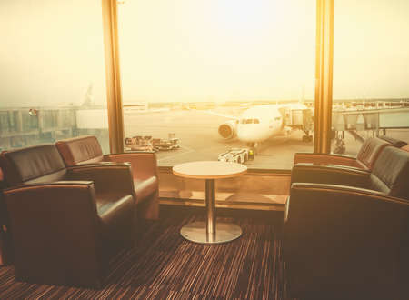 Departure lounge at the airport with seating and table with aircraft preparing for flight in the background