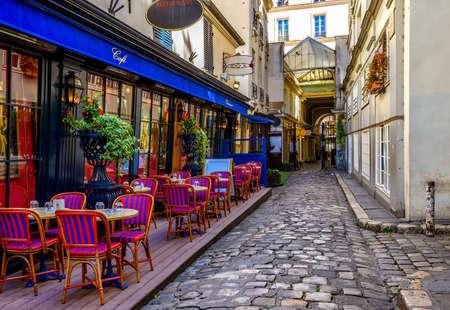 Przytulna ulica ze stołami kawiarnianymi w Paryżu, we Francji