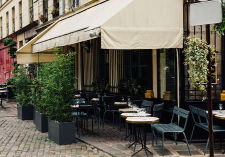 Vista tipica della via parigina con le tavole della brasserie (caffè) a Parigi, Francia