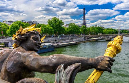 The Nymph reliefs on the bridge of Alexander III with the Eiffel Tower on background at sunset in Paris, France 写真素材