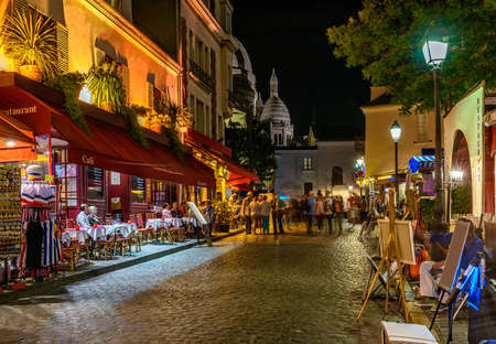Typical night view of cozy street with tables of cafe and easels of street painters in quarter Montmartre in Paris, France