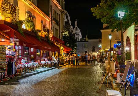 Typische Nachtansicht der gemütlichen Straße mit Tabellen des Cafés und Gestellen von Straßenmalern im Viertel Montmartre in Paris, Frankreich Standard-Bild