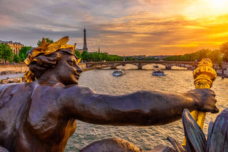 The Nymph reliefs on the bridge of Alexander III with the Eiffel Tower on background at sunset in Paris, France Stock Photo