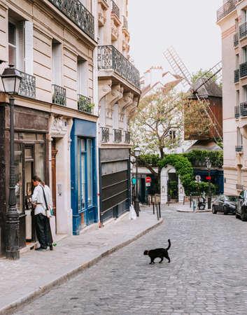 パリ、フランスの四半期モンマルトルのカフェと古いミルのテーブルと居心地の良い通り