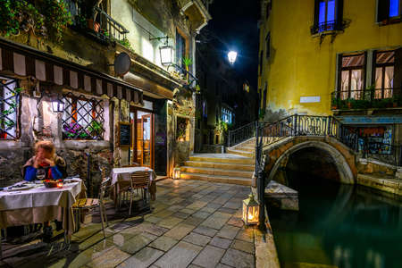 Narrow canal with bridge and tables of restaurant in Venice, Italy. Architecture and landmark of Venice. Night cozy cityscape of Venice. Standard-Bild