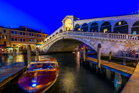 Rialto bridge and Grand Canal in Venice, Italy. Night view of Venice Grand Canal. Architecture and landmarks of Venice. Venice postcard