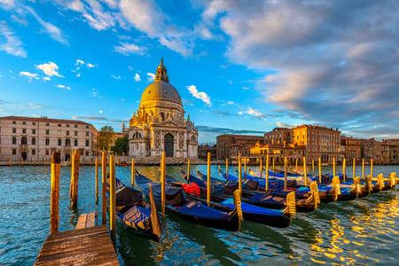 Sunrise view of Canal Grande with Venice gondola and Basilica di Santa Maria della Salute in Venice, Italy