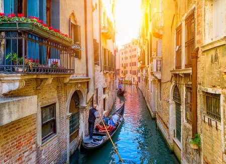 Narrow canal with gondola and bridge in Venice, Italy. Architecture and landmark of Venice. Cozy cityscape of Venice. Reklamní fotografie