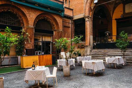 Old narrow street with tables of restaurant in Bologna, Emilia Romagna, Italy Reklamní fotografie