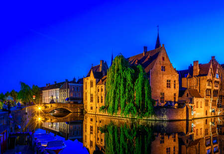 Classic view of the historic city center of Bruges (Brugge), West Flanders province, Belgium. Night cityscape of Bruges. Canals of Brugge