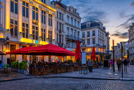 Old street with tables of cafe in center of Brussels, Belgium. Night cityscape of Brussels (Bruxelles). Architecture and landmarks of Brussels. Reklamní fotografie