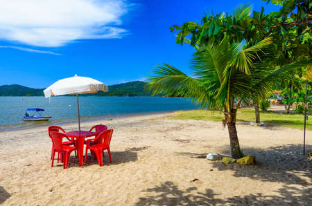 Jabaquara beach with umbrella and chairs in Paraty, Rio de Janeiro, Brazil. Paraty is a preserved Portuguese colonial and Brazilian Imperial municipality