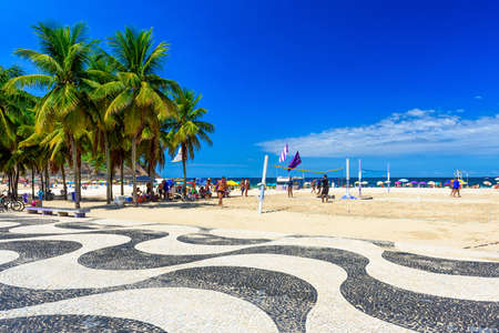 View of Copacabana beach with palms and mosaic of sidewalk in Rio de Janeiro, Brazil. Copacabana beach is the most famous beach in Rio de Janeiro. Sunny cityscape of Rio de Janeiro Фото со стока