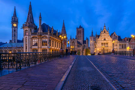 Medieval city of Gent (Ghent) in Flanders with Saint Nicholas Church and Gent Town Hall, Belgium. Nigth cityscape of Gent. Banco de Imagens