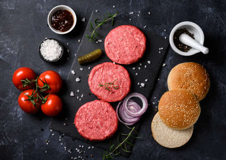 Raw ground beef meat burger steak cutlets with salt, rosemary, bun and tomatoes on dark background