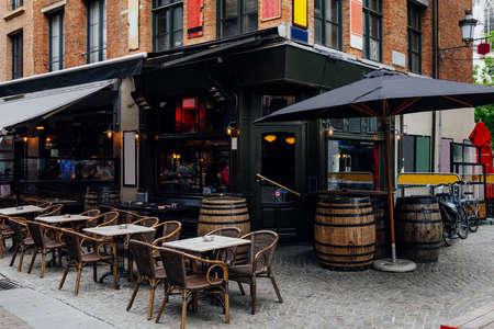 Old street with tables of cafe in historic city center of Antwerpen (Antwerp), Belgium. Cozy cityscape of Antwerp. Architecture and landmark of Antwerpen