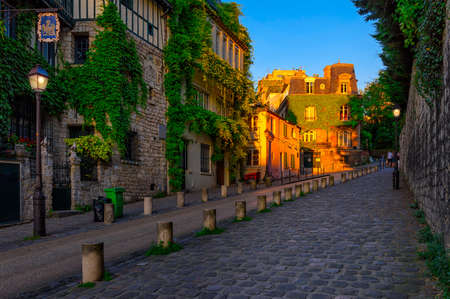 Sunset view of cozy street in quarter Montmartre in Paris, France