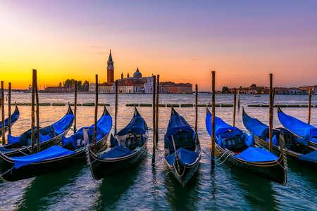 Sunrise in San Marco square with San Giorgio Maggiore island, Venice, Italy. Architecture and landmarks of Venice. Venice postcard with Venice gondolas