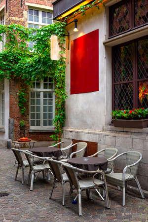 Old street with table of cafe in historic city center of Antwerpen (Antwerp), Belgium. Cozy cityscape of Antwerp. Architecture and landmark of Antwerpen