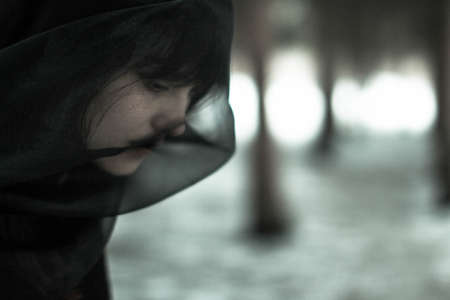 Close-up face of a beautiful young single woman in depression in a black veil, in a black and white concept