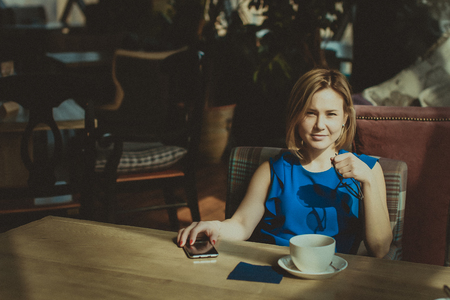 Portrait of a beautiful young woman with a cup of coffee in a restaurant. business lunch