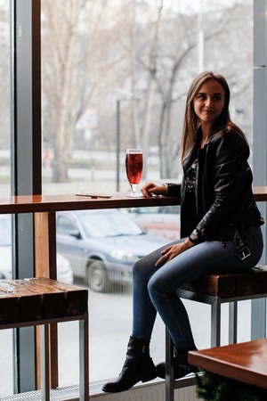 A young beautiful woman is sitting on a bar stool by a large window waiting for lunch